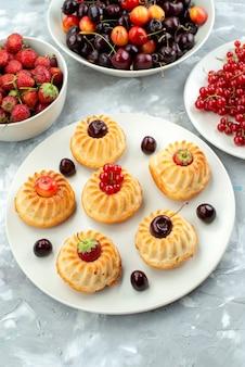 Una vista superior deliciosos pasteles con bayas y frutas dentro de las placas pastel de azúcar de galleta