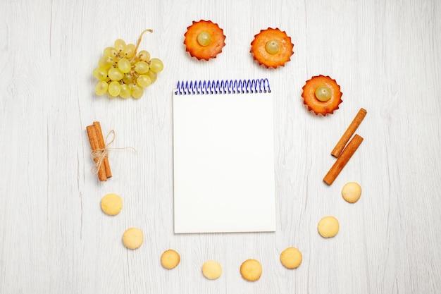 Vista superior de deliciosos pasteles con bloc de notas de uvas y galletas en el escritorio blanco, pastel de frutas, galletas, postre dulce, té