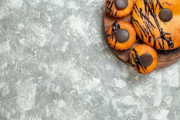 Vista superior deliciosos pasteles con chocolate y glaseado en el piso blanco pastel de postre pastel de té de cacao dulce