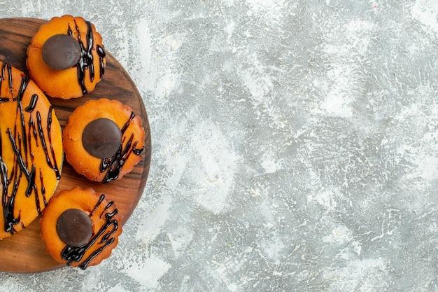 Vista superior deliciosos pasteles con chocolate y glaseado en superficie blanca pastel de postre pastel de té de cacao dulce