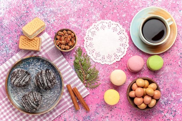 Vista superior deliciosos pasteles de chocolate con taza de té y macarons en rosa