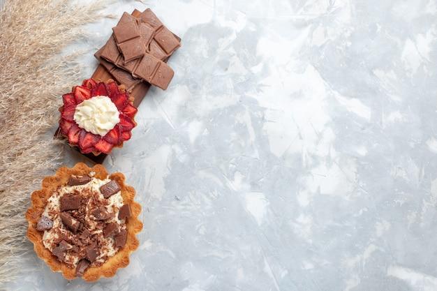 Vista superior deliciosos pasteles cremosos con barras de chocolate en el escritorio blanco pastel galleta dulce azúcar hornear