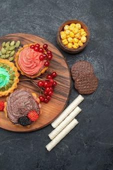 Vista superior deliciosos pasteles cremosos con bayas en galleta de postre de galleta de mesa oscura