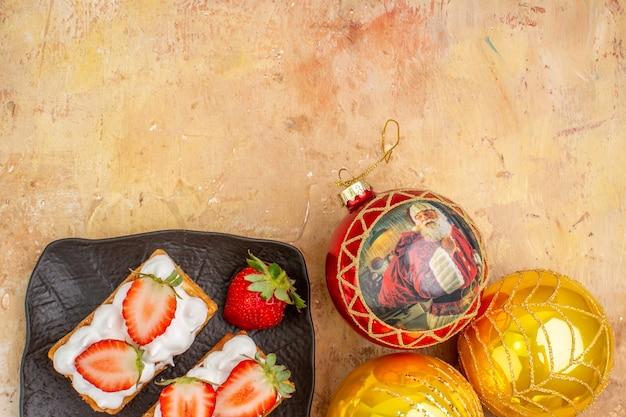 Vista superior deliciosos pasteles cremosos con frutas y juguetes de árbol de vacaciones sobre fondo claro