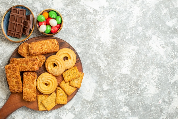 Vista superior deliciosos pasteles con galletas y dulces sobre fondo blanco.