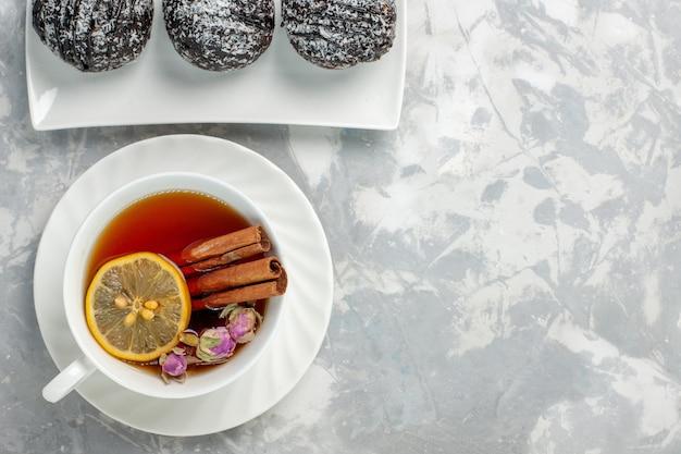 Vista superior deliciosos pasteles con glaseado y una taza de té en el fondo blanco claro pastel de galletas de té hornear pastel dulce de azúcar