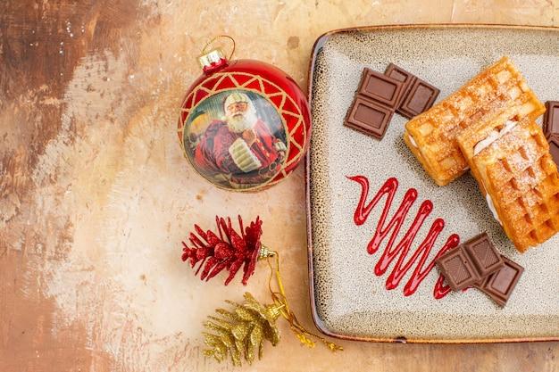 Vista superior deliciosos pasteles de gofres con barras de chocolate en el fondo marrón