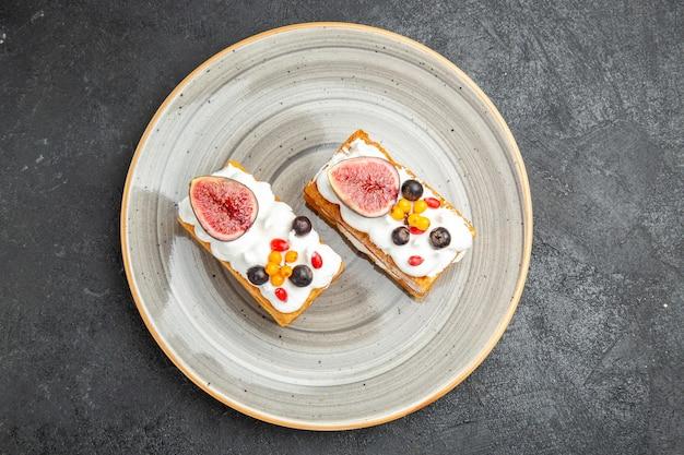 Vista superior deliciosos pasteles de gofres con frutas sobre el fondo oscuro