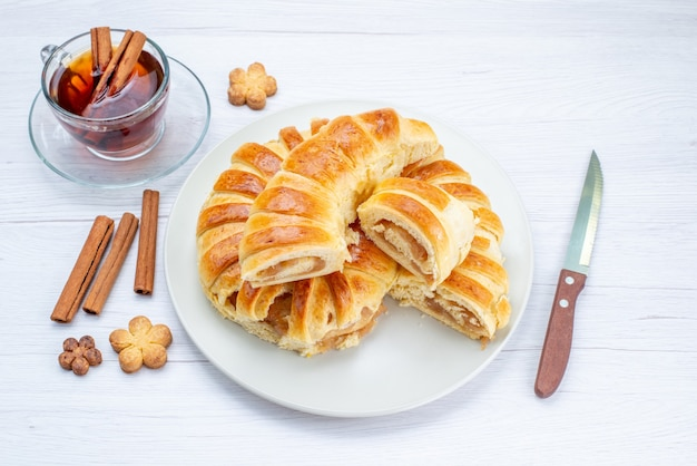 Vista superior de deliciosos pasteles horneados con relleno dulce en rodajas y enteros junto con galletas y té en la mesa de luz, té de pastel de pastelería de galleta