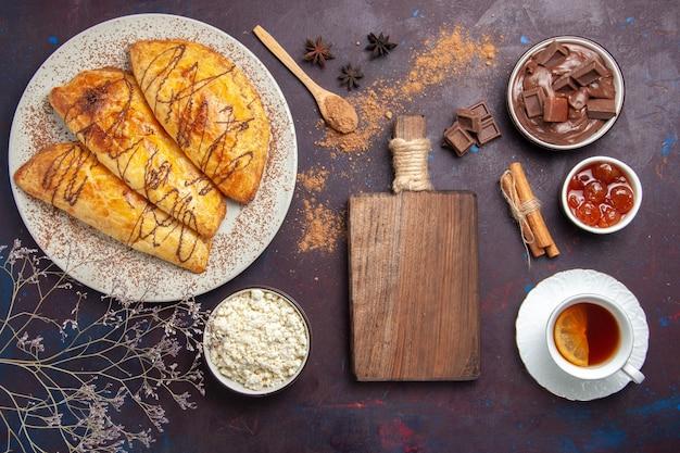 Vista superior de deliciosos pasteles horneados con taza de té y requesón en el espacio oscuro