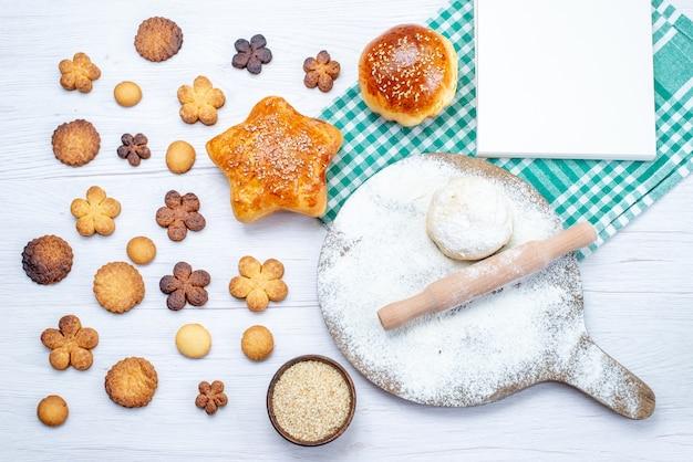 Vista superior de deliciosos pasteles junto con galletas y masa cruda en luz, pastel de galleta galleta azúcar dulce