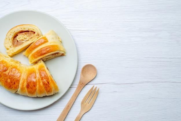 Vista superior de deliciosos pasteles en rodajas dentro de la placa con relleno junto con una cuchara de tenedor de madera en el escritorio blanco, azúcar de galleta de galleta de pastelería