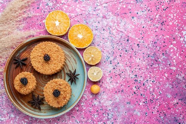 Vista superior de deliciosos pasteles con rodajas de naranjas en superficie rosa