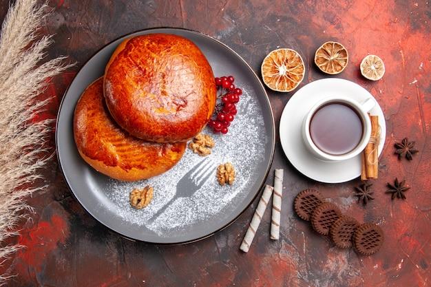 Vista superior de deliciosos pasteles con taza de té en la mesa oscura pastel de pastelería de pastel de dulces