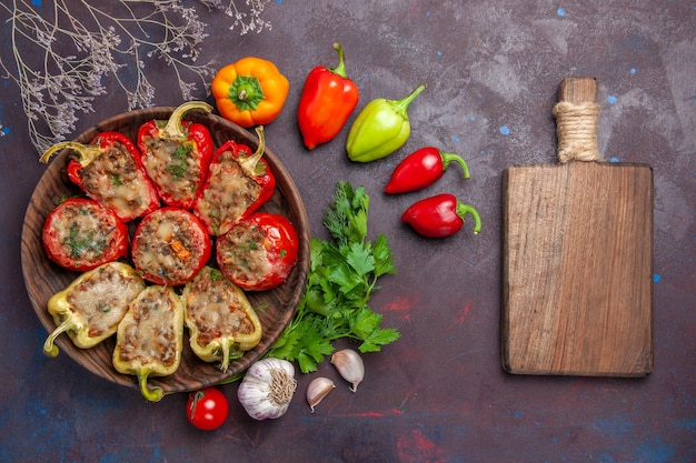 Vista superior deliciosos pimientos al horno plato con carne picada y verduras en el fondo oscuro cena comida hornear sal plato carne