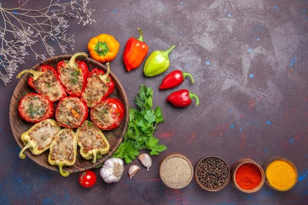 Vista superior deliciosos pimientos al horno plato con carne picada y verduras sobre fondo oscuro plato carne cena hornear comida