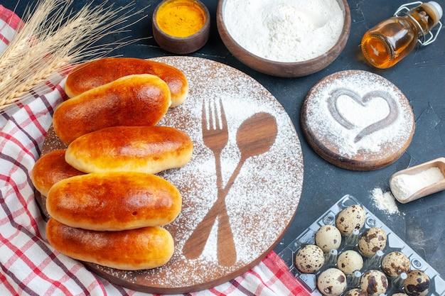 Vista superior de deliciosos rollos de cena, huella de tenedor y cuchara en azúcar en polvo sobre tablero de madera, huevos de codorniz, botella de aceite, cúrcuma y harina en tazones sobre la mesa