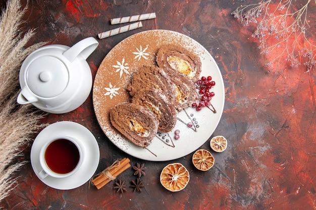 Vista superior de deliciosos rollos de galletas con una taza de té en la mesa oscura