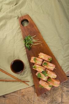 Vista superior de deliciosos rollos de sushi con ingredientes en la mesa de madera