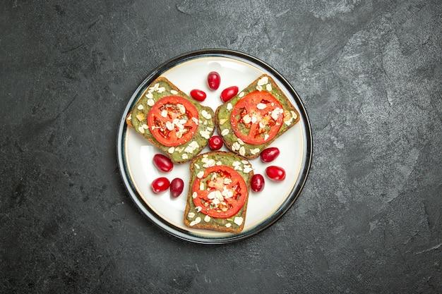 Vista superior deliciosos sándwiches útiles con pasta de aguacate y tomates dentro de la placa en un bocadillo de pan de sándwich de hamburguesa de fondo gris