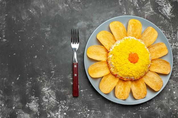 Vista superior desde la derecha de la ensalada con patatas fritas en un plato sobre fondo gris oscuro