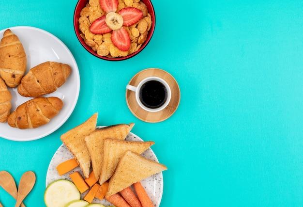 Vista superior del desayuno con cruasanes, tostadas y café con copia espacio sobre fondo azul horizontal