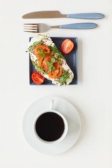 Vista superior en un desayuno gourmet saludable con una deliciosa bruschetta fitness junto a una taza de café negro en la mesa blanca