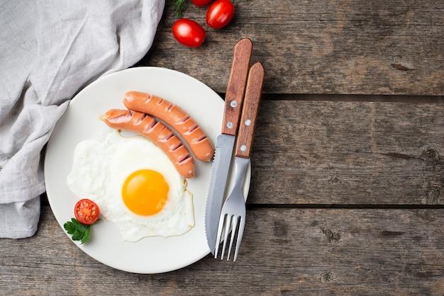 Vista superior del desayuno de huevo y salchichas en un plato con tomates y cubiertos