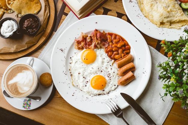 Vista superior desayuno inglés frito huevo frijoles salchichas tocino y taza de café sobre la mesa