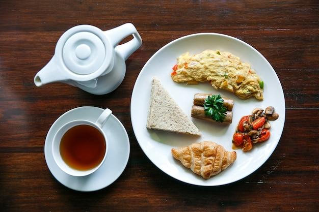 Vista superior del desayuno inglés con una taza de té en la mesa de madera