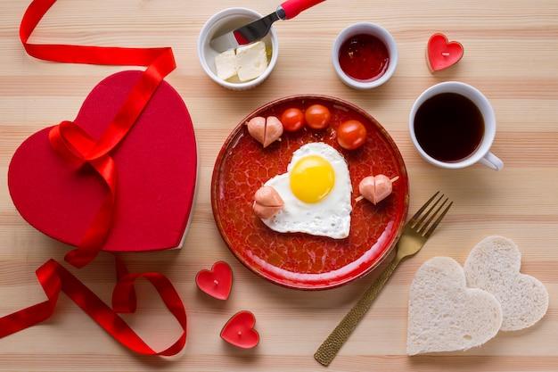 Vista superior del desayuno romántico con café y huevo en forma de corazón.