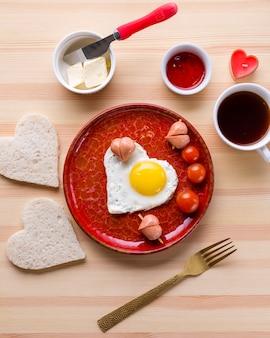 Vista superior del desayuno romántico y huevo en forma de corazón con tostadas