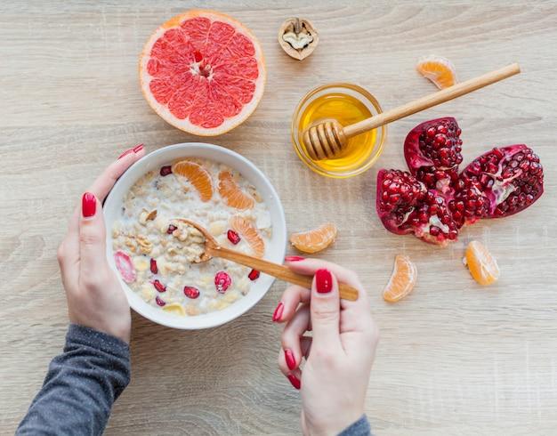 Vista superior desayuno saludable y manos cogiendo cereales