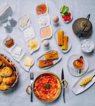 Vista superior desayuno servido mesa huevos revueltos con tomates en una sartén con panqueques queso crema agria mermelada miel y un vaso de té