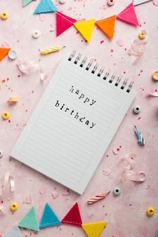 Vista superior del deseo de feliz cumpleaños en el cuaderno con guirnalda