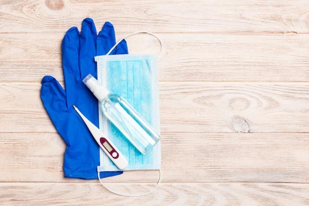 Vista superior del desinfectante de manos con alcohol, guantes de látex, termómetro digital y máscara quirúrgica en la pared de madera. concepto de equipo de protección antivirus con espacio de copia