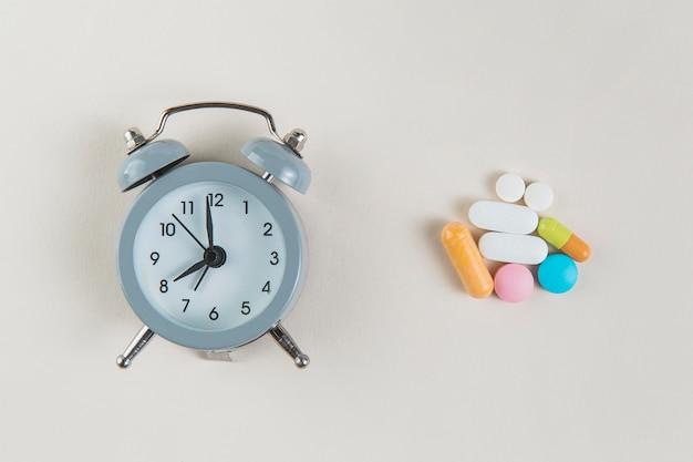 Vista superior despertador con medicamento sobre la mesa