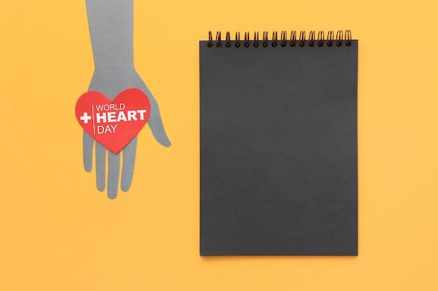 Vista superior del día mundial del corazón con bloc de notas