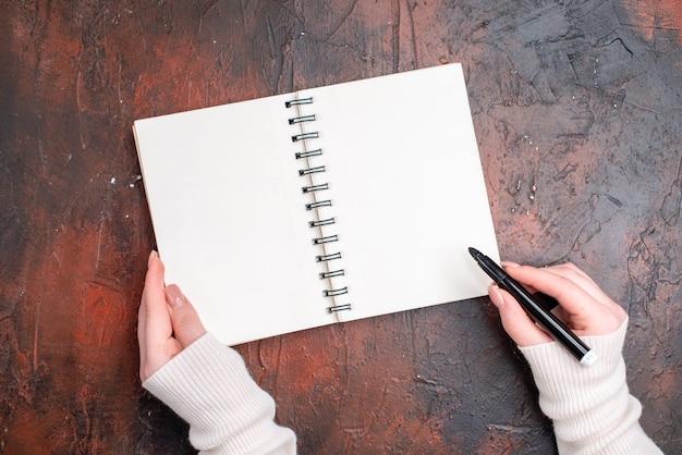 Vista superior dibujo femenino joven en el bloc de notas en la mesa oscura