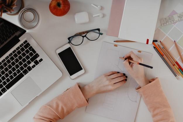 Vista superior del dibujo de manos. retrato de herramientas de oficina, lápices, auriculares, portátil y smartphone en blanco.