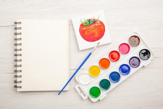 Vista superior dibujo de tomate pequeño con pinturas de colores sobre mesa blanca