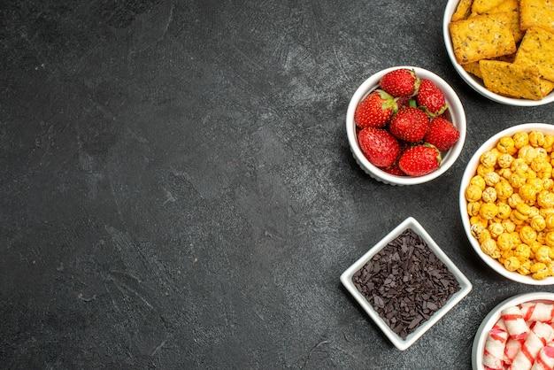 Vista superior de diferentes aperitivos, frutas y galletas.
