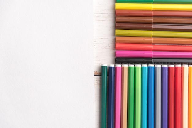 Vista superior de diferentes colores pastel pintura y marcadores en cajas en mesa blanca