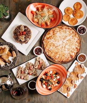 Vista superior de diferentes comidas, como pizza, vegetales, ensalada de grecia, panqueques y otros en el piso claro