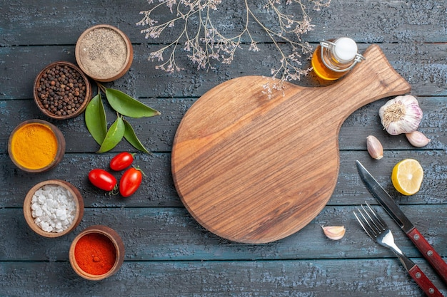 Vista superior de diferentes condimentos con ajo en el escritorio azul oscuro color maduro ensalada de alimentos pimienta picante