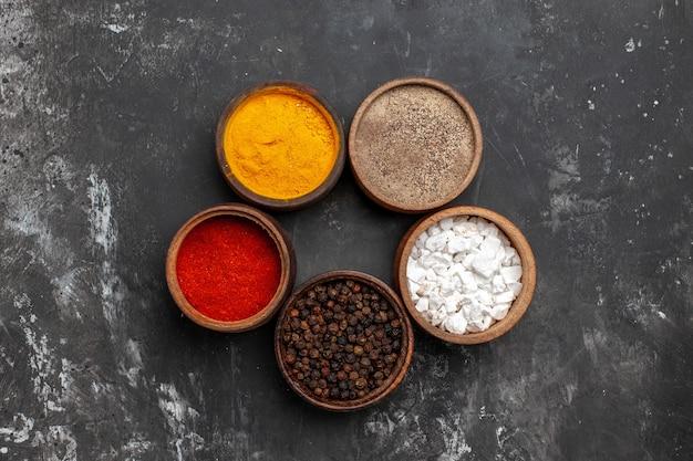Vista superior de diferentes condimentos dentro de pequeñas ollas en la mesa oscura pimienta color especia