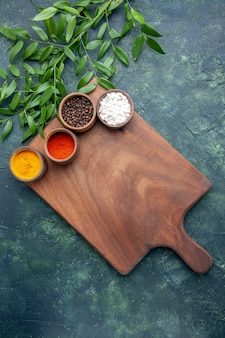 Vista superior de diferentes condimentos con escritorio de madera marrón en la mesa de color azul oscuro, madera de color verde árbol afilado cocina