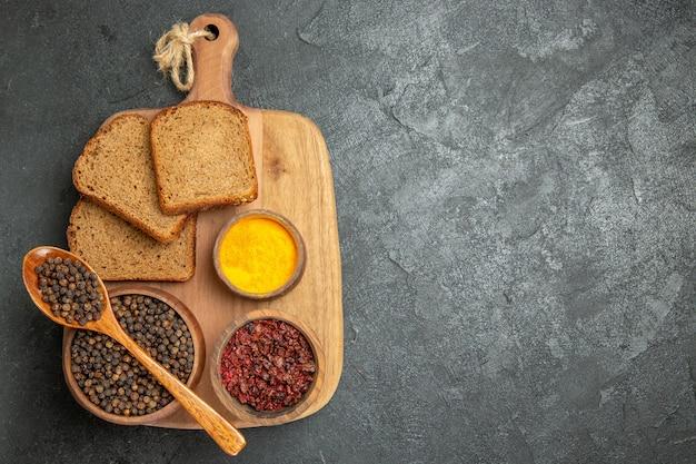Vista superior de diferentes condimentos con panes de pan oscuro en pan de escritorio gris picante caliente