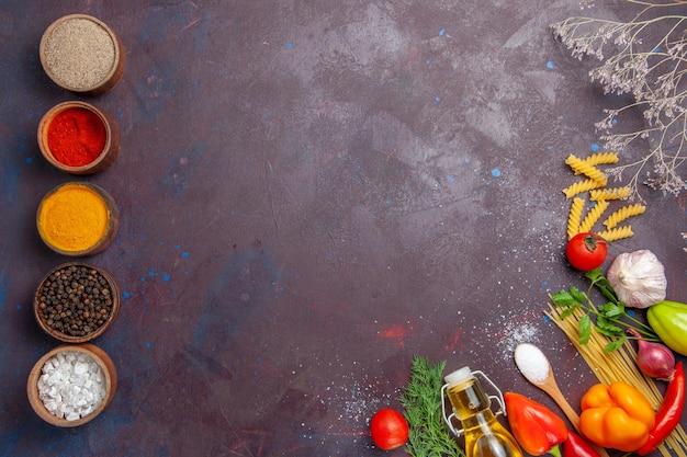 Vista superior diferentes condimentos con pasta cruda sobre fondo oscuro producto ensalada de alimentos crudos dieta saludable