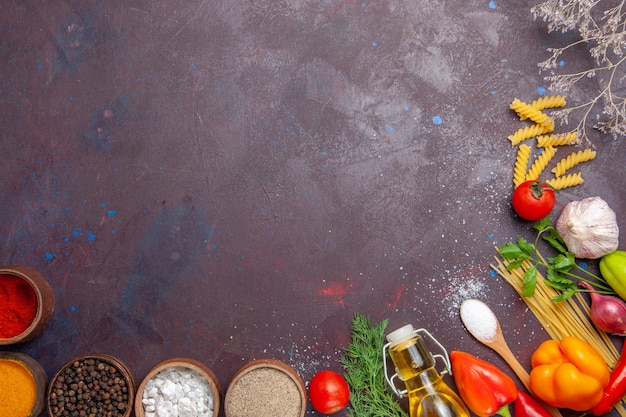 Vista superior de diferentes condimentos con pasta cruda sobre fondo oscuro producto salud ensalada de alimentos crudos